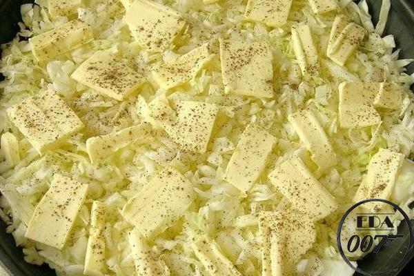 Порежьте сливочное масло на тоненькие пластинки и выложите поверх капусты, и перчите