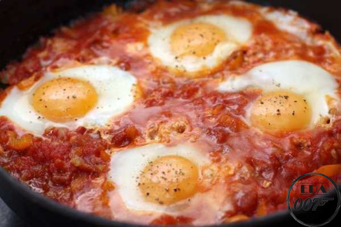 Когда наша жижа закипит, сделайте в ней углубления и в каждое аккуратно вылейте по одному яйцу.