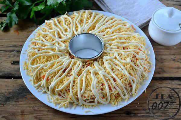 Следующим слоем будет морковь и тертый твердый сыр, который обильно смажьте майонезом.