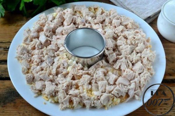 Сверху на яйца с майонезом выложите измельченную куриную грудку и также смажьте ее майонезом
